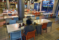 In this Feb. 27, 2020 photo, a customer eats a bowl of soup at a deserted food court in the Koreatown section of Los Angeles. (AP Photo/Richard Vogel)