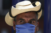 A street vendor wears a mask over his mouth as a precaution against the spread of the new coronavirus in Mexico City, on Feb. 28, 2020. (AP Photo/Fernando Llano)