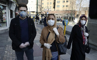 Tehran resident Leila Tayyeb, center, with her husband wearing mask and gloves, speaks with The Associated Press, as a woman walks past, in downtown Tehran, Iran, on Feb. 27, 2020. (AP Photo/Vahid Salemi)