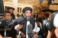 Taliban leader Mullah Abdul Salam Zaeef, center, who served as ambassador to Pakistan during the Taliban's rule speaks to the media in Doha, Qatar, on Feb. 29, 2020. (AP Photo/Hussein Sayed)