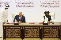 U.S. peace envoy Zalmay Khalilzad, left, and Mullah Abdul Ghani Baradar, the Taliban group's top political leader sign a peace agreement between Taliban and U.S. officials in Doha, Qatar, on Feb. 29, 2020. (AP Photo/Hussein Sayed)