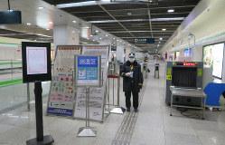 中国・上海の地下鉄の自動改札付近で利用者の検温のため待機する駅関係者=上海市内で2020年2月13日、工藤哲撮影