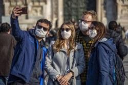 マスクで写真を撮るイタリアの観光客 Bloomberg