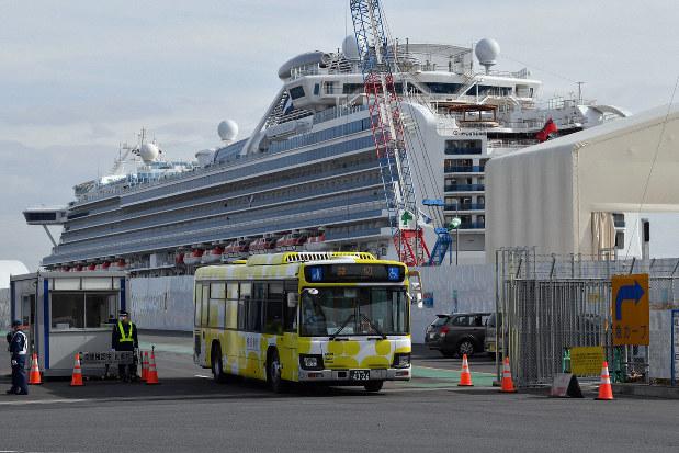 クルーズ船「ダイヤモンド・プリンセス」から下船した乗客らを乗せて出発するバス=横浜市鶴見区で2020年2月19日、北山夏帆撮影