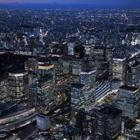 1964年東京オリンピックの聖火が到着した都庁舎があった場所には現在、東京国際フォーラム(左下)が建つ。周辺の丸の内地区は開発が進み、街の明かりがきらめく高層ビル街へと変貌した。左は皇居=東京都中央区で2020年2月27日、本社ヘリから手塚耕一郎撮影