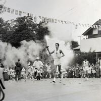 当時、大勢の人が見守ったこの場所を駆け抜ける遠藤さん(中央)=1964年10月8日(本人提供)