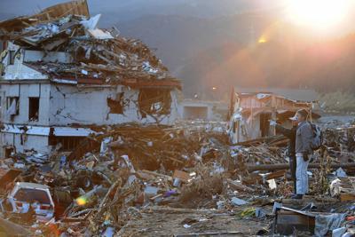 津波に飲み込まれた市街地を眺める人たち=岩手県陸前高田市で2011年3月12日午後5時8分、兵藤公治撮影