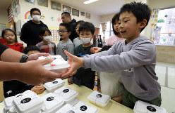 新型コロナウイルスの影響で学校が休校となったため学童保育に通い、弁当会社から無償で提供された弁当をうれしそうに受け取る子供たち=東京都江東区で2020年3月6日午後0時21分、小川昌宏撮影