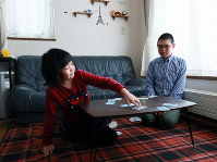 Masaki and Akemi Higashihara, both elementary school students, are seen playing cards at home while both their parents are out working, in Higashi Ward, Sapporo, on March 6, 2020. (Mainichi/Taichi Kaizuka)
