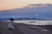 A woman who lost her classmate in the 2011 Great East Japan Earthquake looks out to the ocean, in Higashimatsushima, Miyagi Prefecture, on the morning of March 11, 2020.