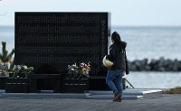 Ai Kikuchi, 29, whose grandfather died and whose grandmother remains missing after the 2011 Great East Japan Earthquake, looks out to the ocean after praying for her grandparents in front of a monument in the city of Soma, Fukushima Prefecture, on March 11, 2020. She said the nine years since the disaster had passed