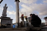 A 59-year-old man prays in front of a monument for the victims of the 2011 Great East Japan Earthquake and resultant tsunamis at the Arahama district in Sendai's Wakabayashi Ward, on March 11, 2020.
