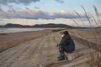 Kazutoshi Takagi, 43, a resident of Oshu, Miyagi Prefecture, looks out to the ocean in the prefectural city of Higashimatsushima, on March 11, 2020. He quit his job soon after the 2011 Great East Japan Earthquake and moved to Miyagi from Tochigi Prefecture in eastern Japan to help areas hit by the disaster.