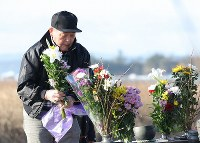 Nobuyuki Sato, 69, offers flowers at a monument for the victims of the 2011 Great East Japan Earthquake and its resultant tsunamis at the Suginoshita district in Kesennuma, Miyagi Prefecture, on March 11, 2020. His wife Saiko, then 60, was deemed missing, but her skeletal remains were found in 2018.