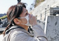 Yuko Iwama, 51, who lost her father Tsutomu, then 77, in the tsunami after the 2011 Great East Japan Earthquake, is seen visiting his grave in Otsuchi, Iwate Prefecture, on March 11, 2020.