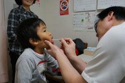 せきや発熱の症状で診察を受ける子ども=東京都港区で