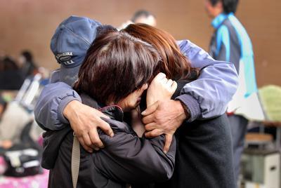 連絡が取れなかった女性(手前左)を捜しに盛岡市から岩手県陸前高田市の避難所を訪れ、再会を果たした娘(右)。また兄(奥)は自らも被災しながら避難所を巡り女性の無事を確認。3人は数分間しっかりと抱き合った=2011年3月14日午後2時57分、小川昌宏撮影