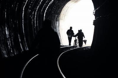 道路が寸断されJR大船渡線のトンネルを歩いて市の中心部に向かって歩く人たち=宮城県気仙沼市で2011年3月15日、小関勉撮影