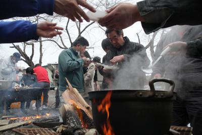 避難住民が自主的に始めた炊き出しで配られた魚料理を食べる住民。温かい食事は久しぶりだ=岩手県宮古市で2011年3月17日午後3時58分、和田大典撮影