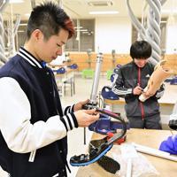 陸上教室に向けてスポーツ義足の準備をする学生たち=新潟市北区で2020年1月31日午後6時26分、藤井達也撮影