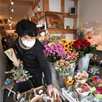 花の定期便サービス「Bloomee LIFE(ブルーミーライフ)」の提携店「フラワーギャラリー スローダンス」で配送に向けて花束を作る山崎悟志さん。「介護施設での教室の中止、予約のキャンセルもあって、2月からの売り上げは例年の3割減。どの業界も厳しいと思いますが、花を飾って少しでも癒やされてくれたら」と話した=東京都世田谷区で2020年3月11日、竹内紀臣撮影