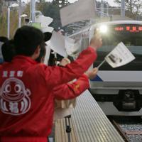 今月避難指示が一部解除された双葉町などで常磐線の運転が再開され、双葉駅に到着する列車を迎える同町役場職員ら=福島県双葉町で2020年3月14日午前6時38分、和田大典撮影