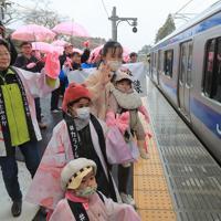 JR常磐線が全線で運行再開され、夜ノ森駅で名所の桜並木をイメージした桜色の傘やタオルを振って列車を見送る人たち=福島県富岡町で2020年3月14日午前9時58分、和田大典撮影