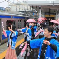 JR常磐線が全線開通し、夜ノ森駅で名所の桜並木をイメージしたピンクの傘やタオルを手に、よさこい踊りで列車を迎える人たち=福島県富岡町で2020年3月14日午前10時21分、和田大典撮影