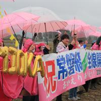 今月避難指示が一部解除された富岡町などで常磐線の運転が再開され、名所の桜並木をイメージしたピンク色の傘や横断幕を手に、特急ひたちに「おかえり」と呼びかける人たち=福島県富岡町で2020年3月14日午前11時8分、和田大典撮影