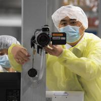 中韓からの入国制限が強化される中、韓国便到着を前に体温を測るサーモグラフィーを調整する検疫官ら=成田空港で2020年3月9日午前8時3分、手塚耕一郎撮影