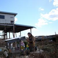 4日に避難指示が解除されたばかりの地域で、自宅跡地の祭壇に向かって手を合わせる志賀一郎さん(72)。妻さち子さん(当時63歳)と孫の仁美ちゃん(4カ月)が行方不明のままだ。9年経った今も、破壊された作業場など津波の傷跡が当時のまま残る。「早くでてきてくれ、って言うしかない」=福島県双葉町で2020年3月11日午前11時20分、小川昌宏撮影