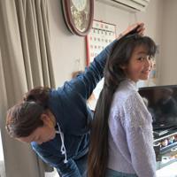 消防団員として避難を呼びかけながら津波で亡くなった高橋昌照さん(当時37)の娘、心陽さん(11)(右)の髪の長さを測る妻の陽香さん(46)。心陽さんは1歳の時に被災したため父親の記憶はないが、「パパが最後になでてくれた頭だから」と生まれてから一度も後ろ髪を切っていない。髪の長さは1.2メートルになっていた=仙台市宮城野区で2020年3月11日午後3時27分、北山夏帆撮影