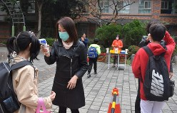 校門で子供たちの体温を測定する教師や保護者ら=台北市中山区の長安小で2020年3月11日、福岡静哉撮影