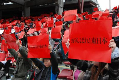 東日本大震災の被災地を支援しようと、プロ野球・広島が開催した支援試合で、「がんばれ!東日本」と書かれたポスターを掲げて応援メッセージを送る人たち=広島市南区のマツダスタジアムで2011年3月21日午後1時23分、寺岡俊撮影