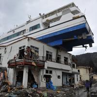 津波で民宿の屋根の上に打ち上げられた観光船「はまゆり」=岩手県大槌町で2011年3月23日午後1時3分、西本勝撮影