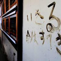 津波に襲われた宮城県東松島市の市立大曲小の廊下に書かれた被災者を励ます泥で書かれたメッセージ=2011年3月23日午前9時4分、梅村直承撮影