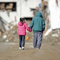 家も道路も何もかもが破壊された街中を手をつないで歩く男性(右)と孫。「避難所にずっといると息が詰まるから」と二人は流された自動車を探しまわっていた=岩手県陸前高田市で2011年3月23日午前8時46分、宮間俊樹撮影