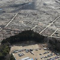 津波で大きな被害を受けた岩手県陸前高田市の市街地(後方)、手前は避難所になっている学校の校庭で建設が進む仮設住宅=2011年3月23日午後2時4分、本社ヘリから岩下幸一郎撮影