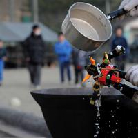 「避難所にいる小学生が喜ぶかなと思って」と、被災地から使えそうなおもちゃのロボットを拾って、廃材を燃やして沸かした湯をかけて泥を落とす男性。避難所となっている小学校の校庭では子どもたちが元気に遊びまわっていた=岩手県陸前高田市で2011年3月23日午後3時27分、宮間俊樹撮影