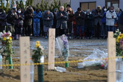 津波の犠牲者を土葬(仮埋葬)し、冥福を祈る遺族たち。震災直後、宮城県東松島市では火葬が追いつかず仮埋葬せざるを得なかった=2011年3月26日午後4時8分、丸山博撮影