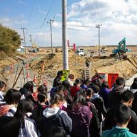 5人の園児が亡くなっているのが見つかった現場近くで黙とうする香川県から訪れた高校生ら。周辺では復旧工事が本格化し、当時の悲惨な光景を想像することが難しくなってきた=宮城県石巻市で2016年3月26日、佐々木順一撮影