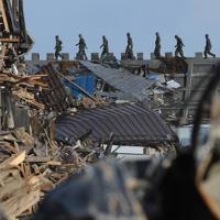 防潮堤の上を隊列を組んで歩く自衛隊員=岩手県宮古市田老で2011年3月28日午後4時、金澤稔撮影
