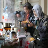 前年3月に廃校となった大原中学の廊下で朝食を作る女性たち。「大谷川浜地区の住人は一致団結して自分たちで生活できるたくましさがあるんです」=宮城県石巻市で2011年3月28日午前6時13分、梅田麻衣子撮影