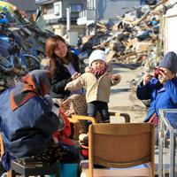 曽祖父母、祖父、母と海からすぐ近くに住んでいた1歳の蓮ちゃん(中央)。津波は1階の階段の上まで押し寄せたが、2階に逃れ無事だった。近所は全壊の家も多く、残った住民が物資を持ち寄って朝ごはんを食べ、震災直後を耐えていた=宮城県石巻市で2011年3月28日、梅村直承撮影