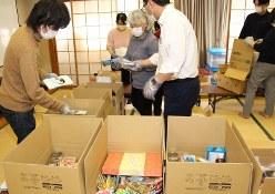 ひとり親家庭に配る食料などを箱に詰め込むNPO法人「太陽の家」のスタッフら=桑名市で20年3月9日、松本宣良撮影