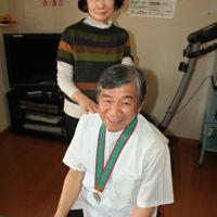 1964年東京大会のメダルを首に掛け「伴走なしで走ります」と話す岩崎博さん(手前)と妻敏子さん=熊本県八代市の自宅で2020年3月6日午後2時38分、山本泰久撮影