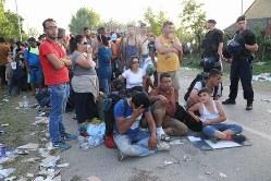 ドイツを目指し、隣国スロベニアとの国境地帯に向かうバスを待つ中東などからの難民たち。メルケル独首相の難民受け入れ決断が欧州難民危機の引き金になった=クロアチア東部のセルビアとの国境の街トバルニクで2015年9月18日、中西啓介撮影