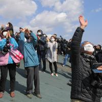 ギリシャのアテネで採火された東京オリンピックの聖火が到着し、上空を飛行するブルーインパルスに歓声を上げる大勢の人たち=宮城県東松島市で2020年3月20日午前11時42分、手塚耕一郎撮影