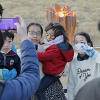 石巻南浜津波復興祈念公園に到着した聖火をともした「復興の火」(奥)をバックに記念撮影する家族連れ=石巻市で2020年3月20日午後3時43分、和田大典撮影