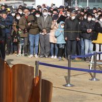 「復興の火」(手前)を見ようと集まった多くの人たち=石巻市で2020年3月20日午後3時38分、宮武祐希撮影